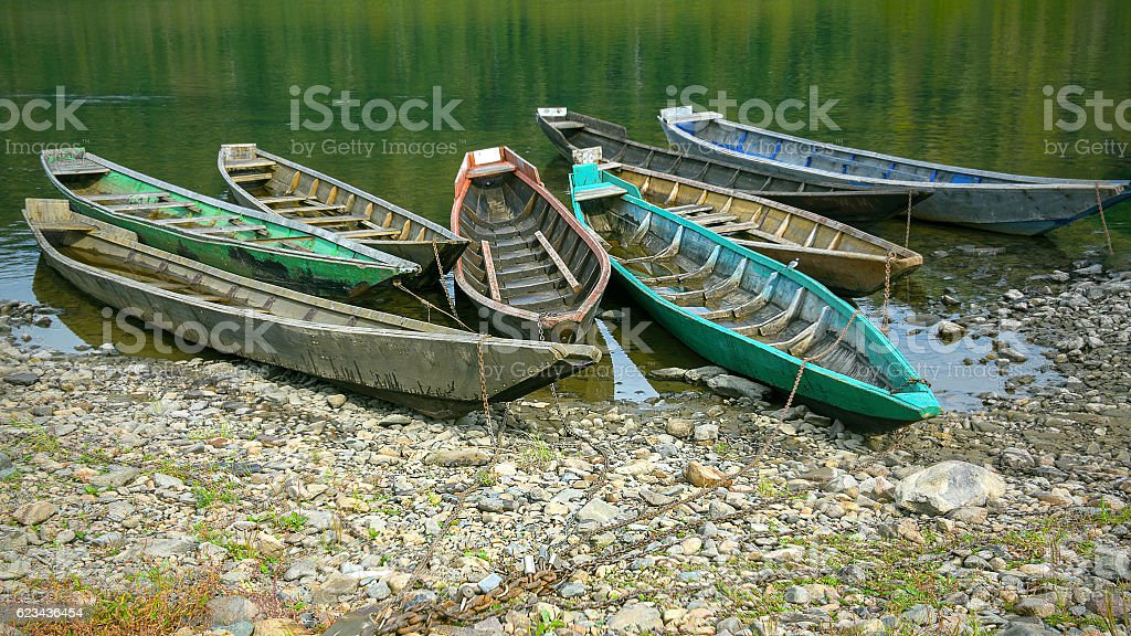 Old wooden boats moored to the bank of the river stock photo