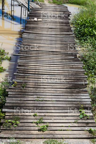 Photo of Old wooden bridge stretching through the canal.