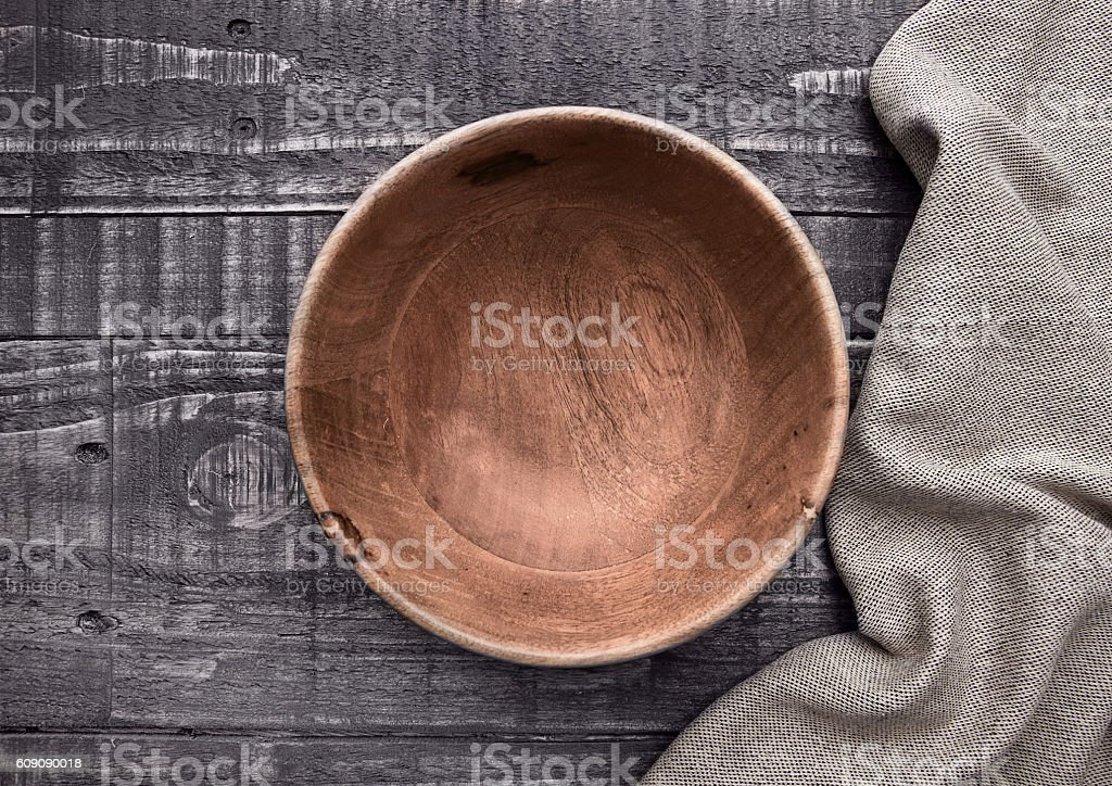 Old wooden brown bowl with kitchen cloth on wood stock photo