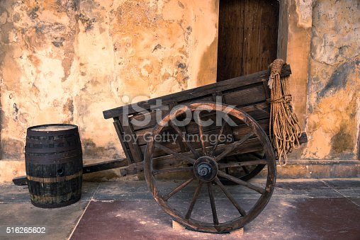 Old wooden cart and barrel next to a weathered wall.