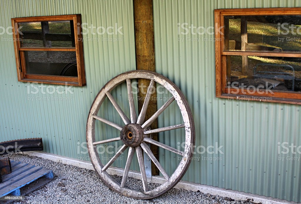 Old Wooden Cart Wheel, Leaning Against Shed stock photo