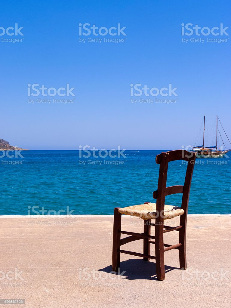 Old wooden chair near the sea - Crete, Greece royalty-free stock photo