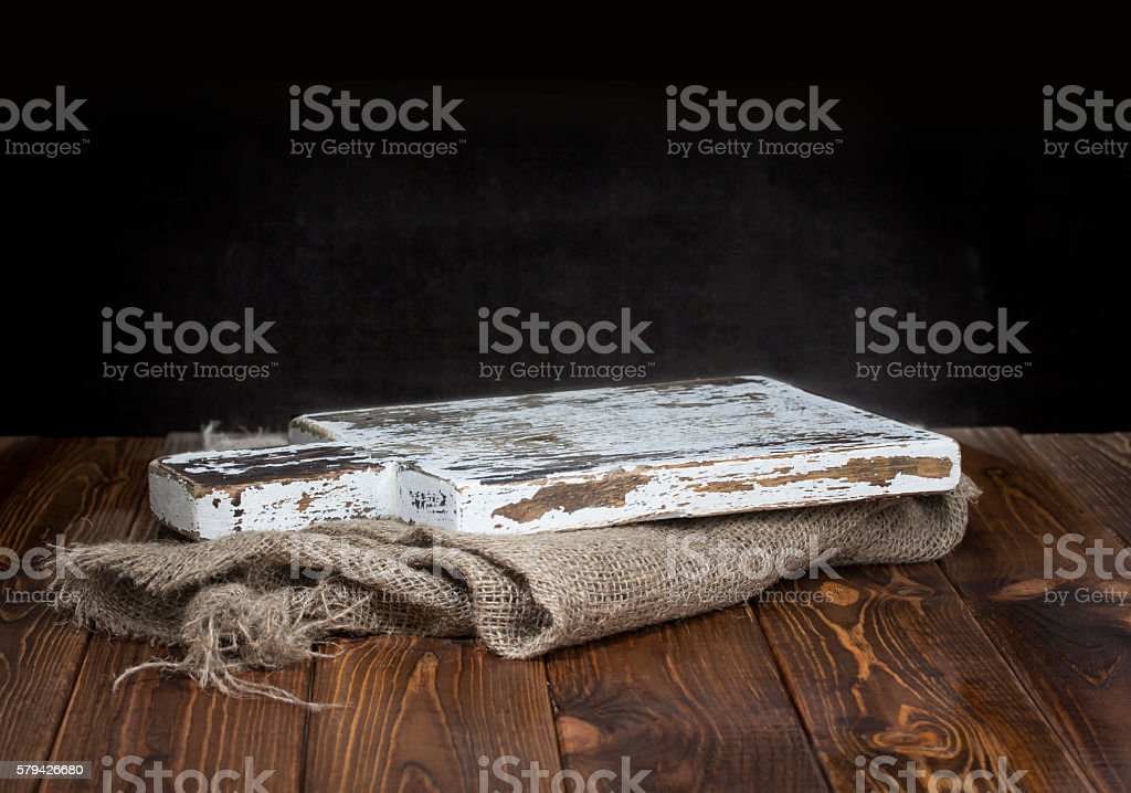 Old wooden chopping board with burlap tablecloth stock photo