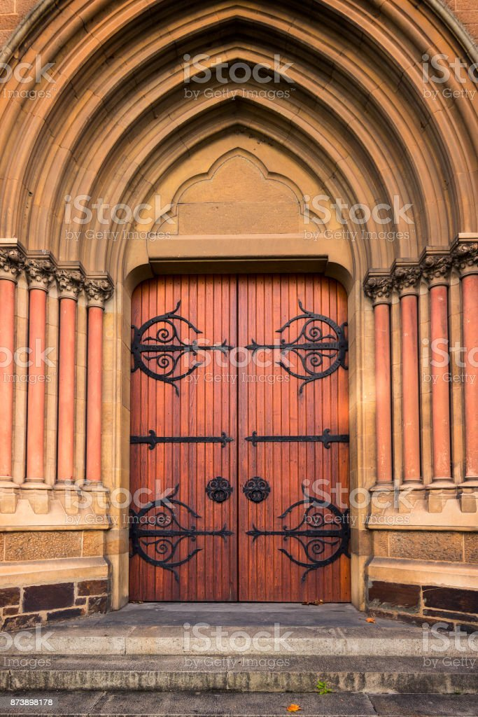 Old wooden church door framed by columns and arches. stock photo