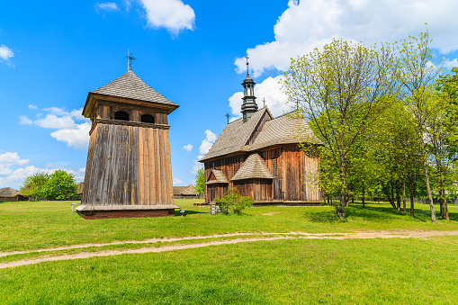 Old wooden church on green meadow in Tokarnia village, Poland