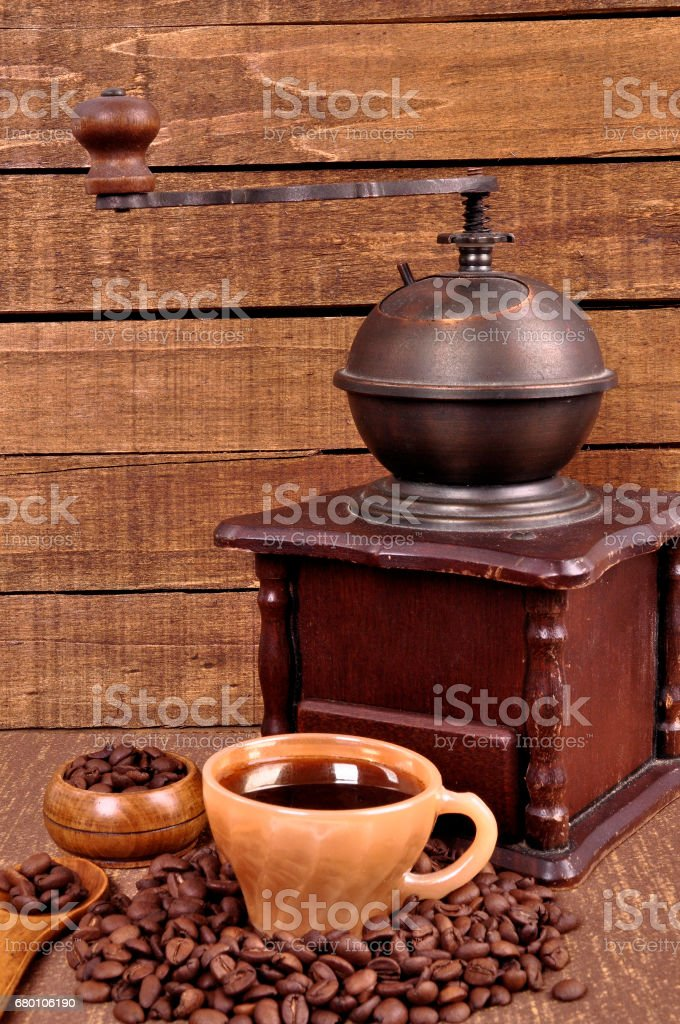 Old wooden coffee grinder and roasted coffee beans on a wooden table . Fresh hot coffee in Cup . stock photo
