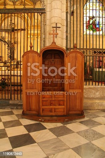 Murcia, Spain- November 16, 2019: Beautiful Old wooden confessional in the cathedral of Murcia. Altar with cross and vintage forged fence in the background