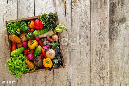 Various types of market fresh sald vegetables packed in an old wooden crate on an old wooden table. Salad vegetables includ types of lettuce, onion, tomato, cucumber, various colour capsicum, potato, radish, beetroot,