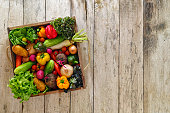 Old wooden crate packed full with fresh market salad vegetables.