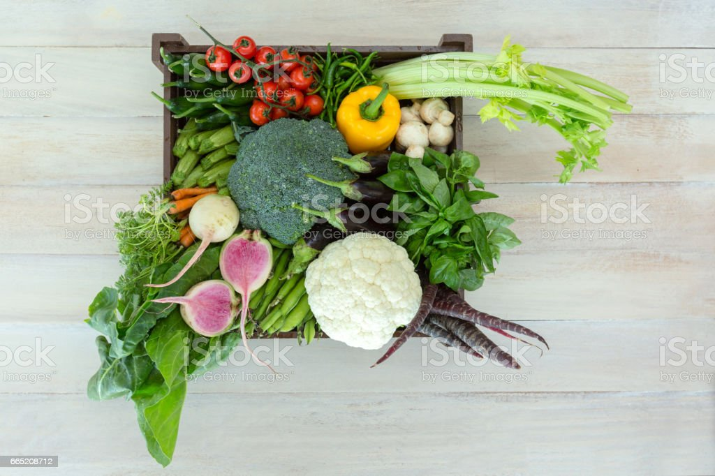 Old wooden crate packed full with fresh vegetables. stock photo