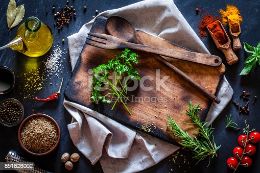 istock Old wooden cutting board with spices and herbs on dark kitchen table 851826002