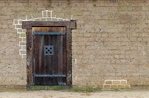old wooden door closeup, front view, brick wall