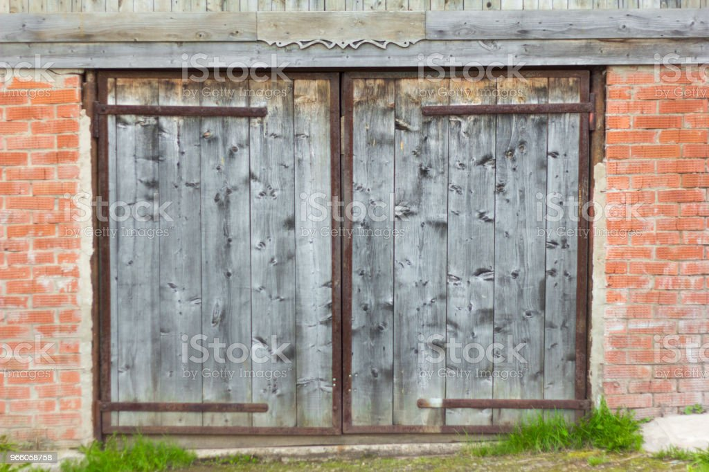 gammal trädörr i en tegelsten garage - Royaltyfri Antik Bildbanksbilder
