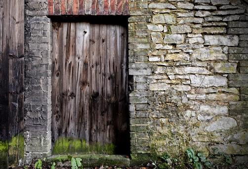 Old wooden door in stone wall