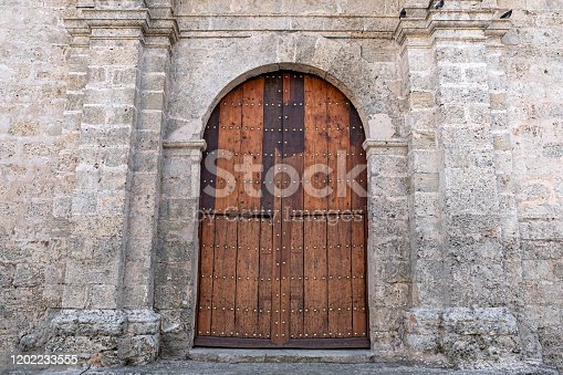 Old wooden door in wall in monastery. The basilica and the monastery of San Francisco de Asis or Saint Francis of Assisi in San Francisco square, Old Havana, Cuba