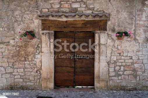istock Old wooden door of a stone building 908317942