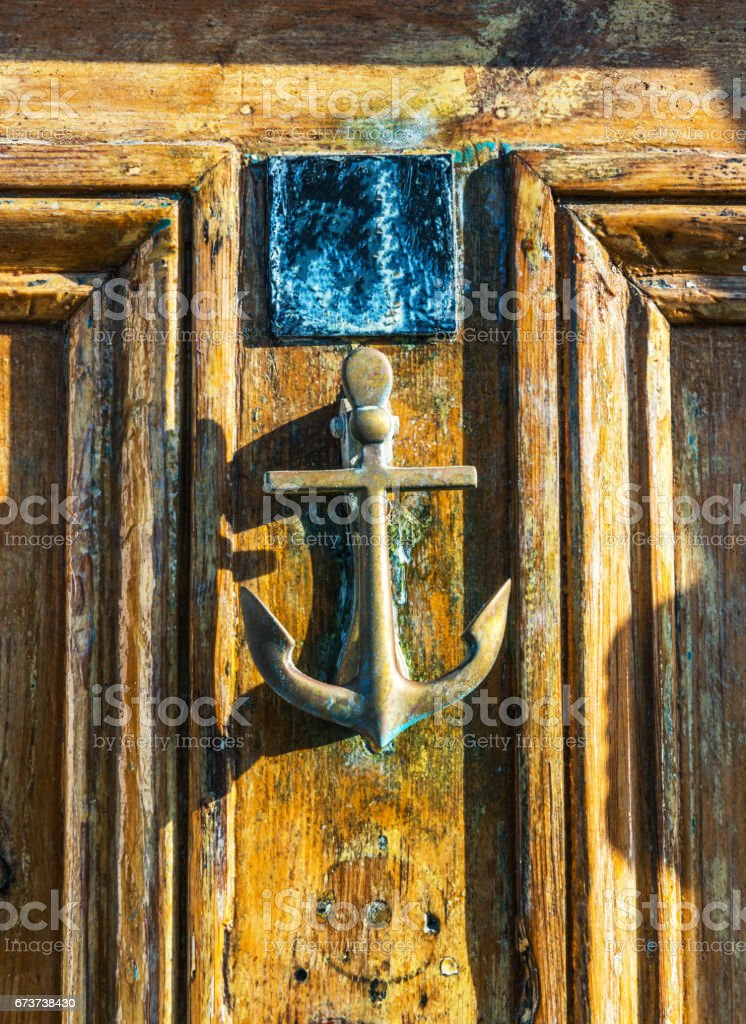 Old wooden door to house with brass knocker shaped like an anchor, sea element royalty-free stock photo