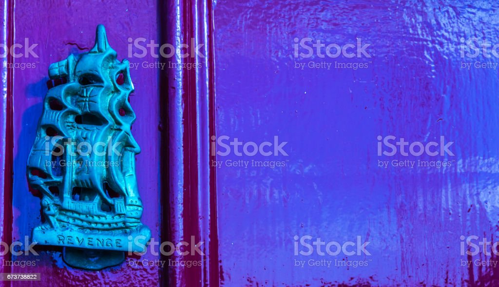 Old wooden door to house with brass knocker shaped sailing ship with inscription of revenge, sea element photo libre de droits