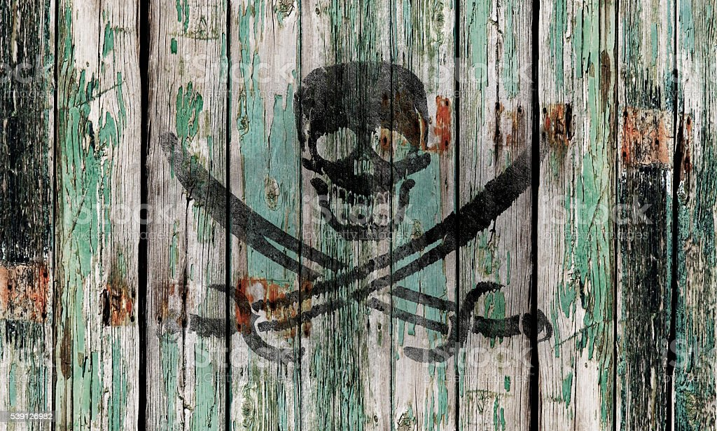 Old wooden door with a skull and swords stock photo