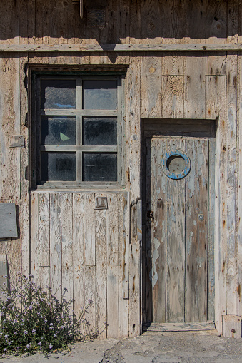 old wooden door with porthole window and a window of a warehouse or barn, wood texture or background, textura de madera o fondo, light wooden planks on a rural barn gate, vintage old warehouse wooden gate and window, wooden texture or background