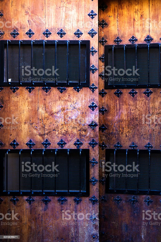 Old wooden door with windows and bars stock photo