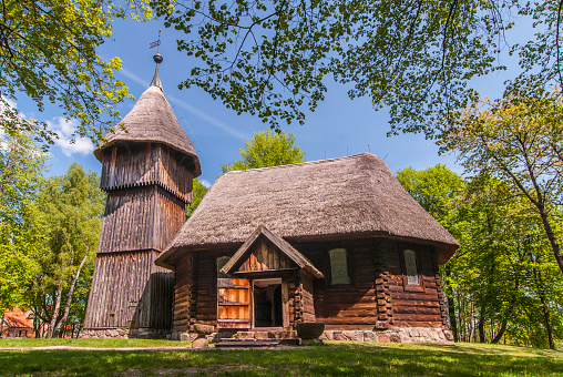 Old wooden evangelic church with and wooden belfry, both from Masuria region, Ethnographic Park in Olsztynek, Poland.