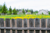 istock Old wooden fence. Background-yellow flowers, village house. 964395924