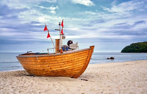 Old wooden fishing boat on sandy beach in the Baltic Sea resort of Binz. Island Rügen, Germany