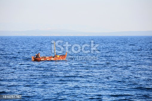 A man is fishing in an old wooden boat