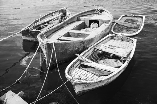 Old wooden fishing boats moored in small port of Avcilar, district of Istanbul, Turkey. Black and white retro stylized photo