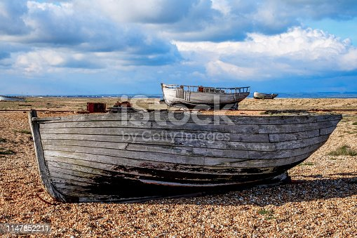 an old wooden fishing boat sitting on a pebble beach, in the back ground on the beach are two more old wooden fishing boats, the pebbel beach is flat and big with a big cloudy blue sky, Dungeness, Kent, England, United Kingdom