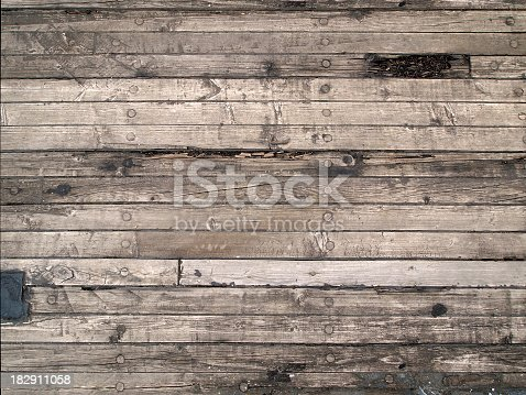 Original, old wooden floor of the sailing boat. Boards are arranged horizontally. Natural scratches and cracks visible.