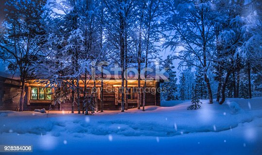 1141614053 istock photo Old wooden forest cabin in winter wonderland scenery at night 928384006