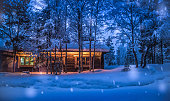 Romantic view of old traditional wooden forest cabin in the woods embedded in scenic northern winter wonderland scenery in beautiful mystic twilight during blue hour at dusk