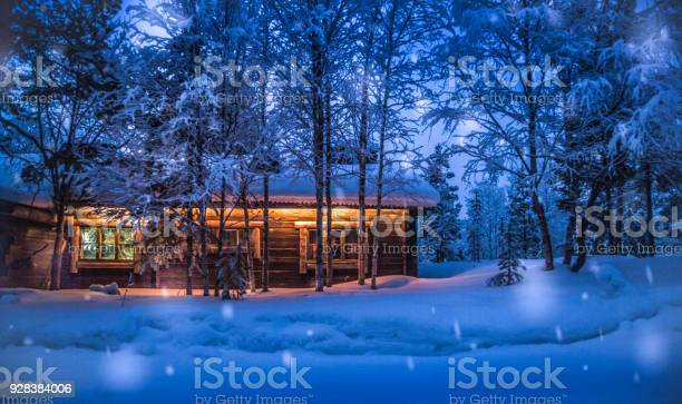 Photo of Old wooden forest cabin in winter wonderland scenery at night