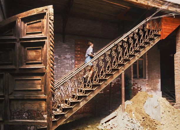altes holztor, eiserne treppe im innenhof alte russische haus in der alten stadt von astrakhan, russland - typisch 90er stock-fotos und bilder