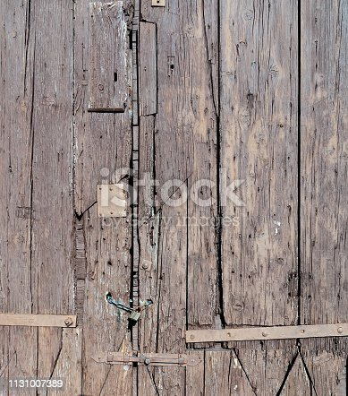 1178501072istockphoto Old wooden gate locked with padlock and chain 1131007389