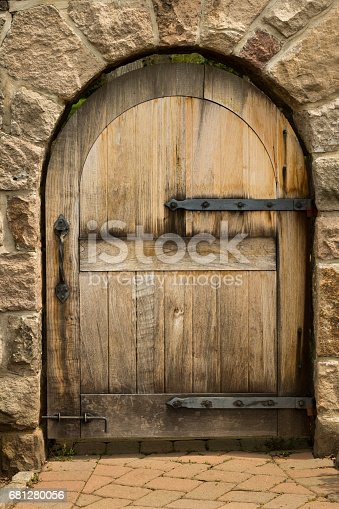 Gate made of heavy lumber and iron within a stone archway entrance. Image shot with Canon Rebel T6s 24 Megapixel DIGIC 6, 24-105mm f/4L IS USM lens, 100 ISO.
