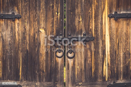 1178501072istockphoto Old wooden gate with a bolt 828200358