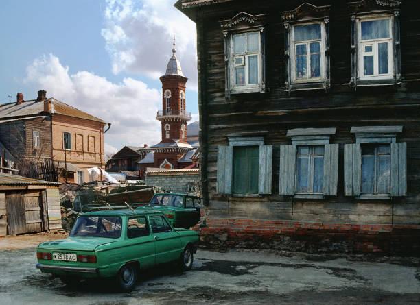 """altes holzhaus von den zeiten des russischen reiches, auf dem hof vor dem haus ist ein familienauto """"zaporozhets"""" - typisch 90er stock-fotos und bilder"""