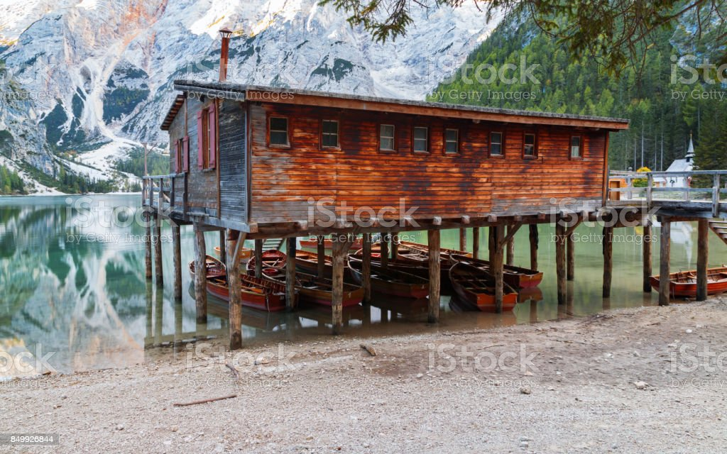 Old wooden house on the Braies lake in the background of Seekofel mountain stock photo