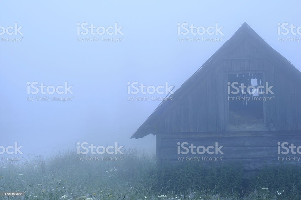 Old wooden hut in blue misty twilight royalty-free stock photo