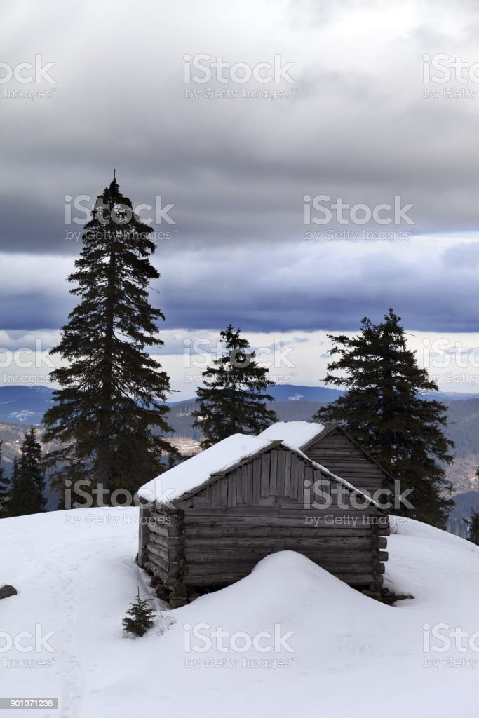 Old wooden hut in winter snow mountains and gray sky with clouds stock photo