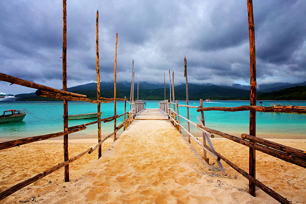 Old wooden jetty on a beautiful tropical beach The view from popular cruise port Mystery Island (Inyeug), Vanuatu across water to neighbouring Tanna Island vanuatu stock pictures, royalty-free photos & images