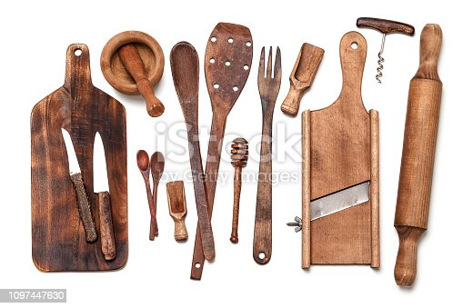 Top view of old wooden kitchen utensils placed in a row on white background. Utensils included in the composition are a cutting board, kitchen knives, mortar and pestle, kitchen spatula, spoons, fork, serving scoops, a corkscrew, a rolling pin and a honey dipper. Predominant colors are brown and white. High key DSRL studio photo taken with Canon EOS 5D Mk II and Canon EF 100mm f/2.8L Macro IS USM.