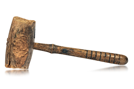 Closeup of an old wooden mallet or hammer, made in Italy, 19th century. Isolated on white background with reflections.