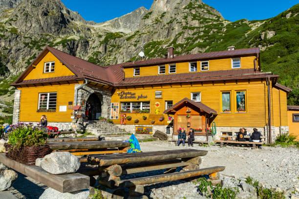 Eski ahşap dağ barınağı (Chata pri Zelenom plese - Horska chata) ve dağlarda güzel bir güneşli sabah turistler. stok fotoğrafı