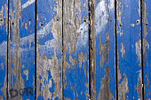 Old wooden painted blue rustic background, paint peeling close up