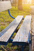 istock Old wooden park bench close-up on blurred green nature background. Backdrop for text sign, copy space vertical banner. 1271666259