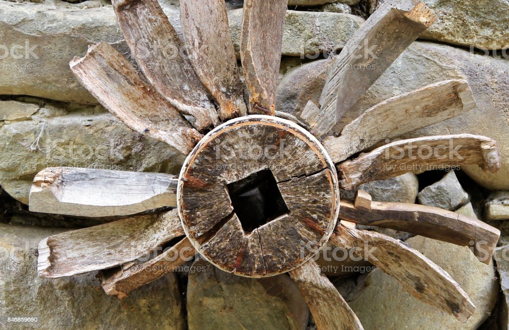 Old wooden piece of watermill mechanism on on a background of stone wall stock photo